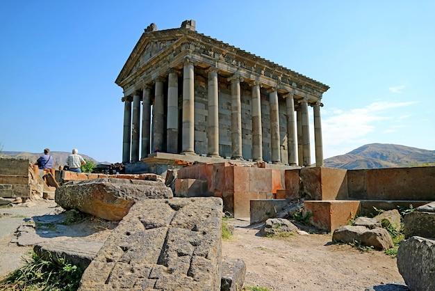 Потрясающий исторический языческий храм гарни с древним крестовым камнем у основания, расположенный в деревне гарни, армения