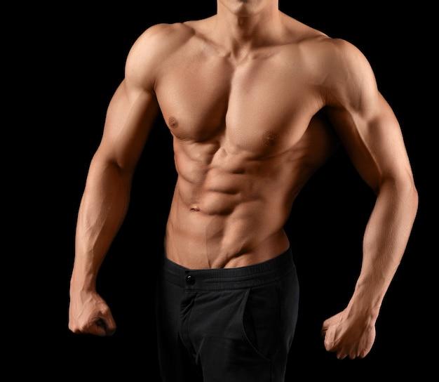 Потрясающий горячий торс мужчины-спортсмена, позирующего на темноте