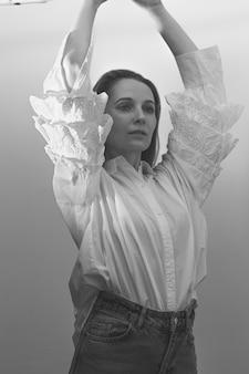 スタイリッシュな白いコットンブラウスにラフとジーンズを両手でポーズをとる見事なインテリジェントスラブ女性。