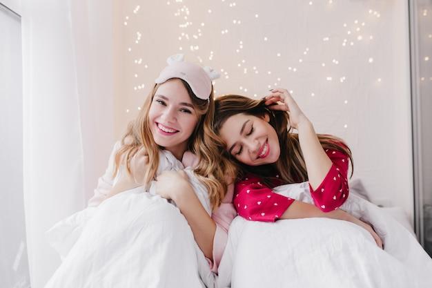 明るいインテリアの部屋で美しい笑顔でポーズをとる見事な女性。ベッドに座って週末の朝を楽しんでいる身も凍るような女の子。