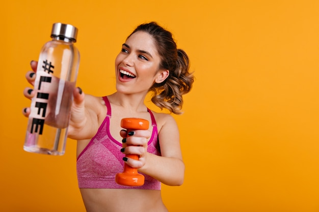 Stunning lady drinking water while training