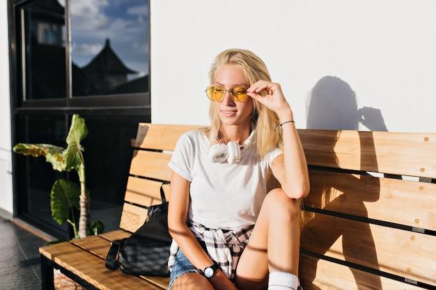 나무 벤치에 앉아 캐주얼 흰색 티셔츠에 멋진 아가씨. 화창한 아침을 즐기는 노란색 선글라스에 꿈꾸는 금발 여자의 야외 초상화.