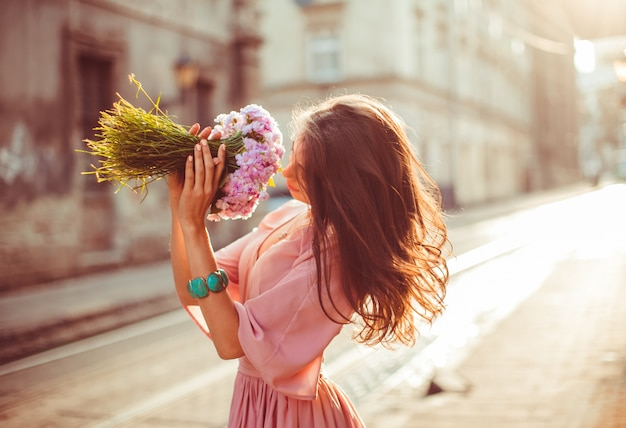 Stunning lady in pink dress poses in rays of morning sun on the