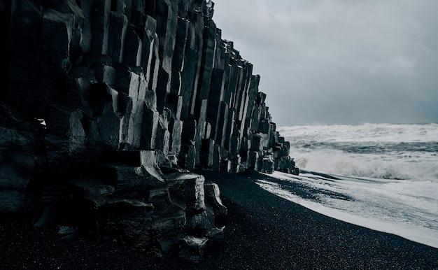 Потрясающий пейзаж, черный песчаный пляж, базальтовые скалы, сильные штормовые волны. морской пейзаж. путешествия, отдых, туризм.