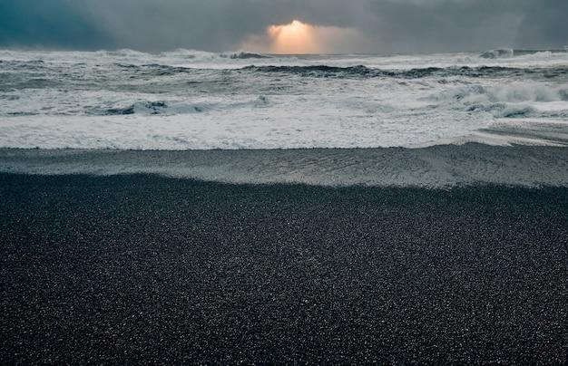 Потрясающий пейзаж, черный песчаный берег, сильные штормовые волны, утренний закат. морской пейзаж. путешествия, отдых, туризм.