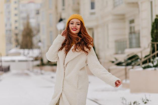 Потрясающая длинноволосая девушка в желтой шляпе позирует на размытой улице. открытый выстрел счастливой дамы имбиря, наслаждаясь зимой.