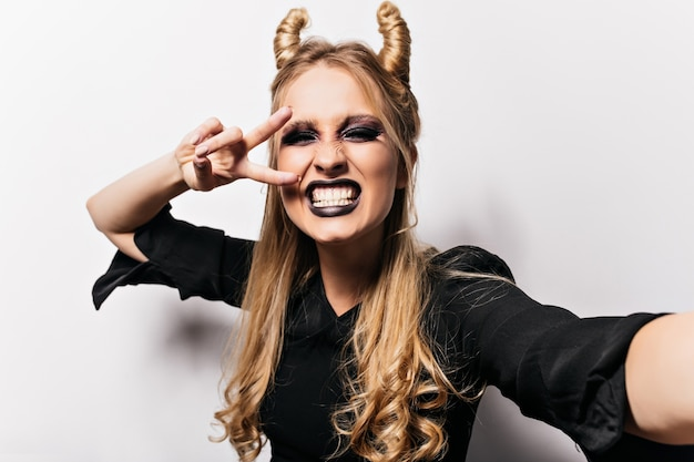 Потрясающая длинноволосая ведьма дурачится на хэллоуин. крытый снимок блондинки, делающей селфи в злом костюме.