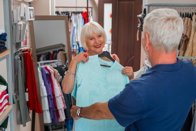 見事な表情。胸にドレスを着たまま夫を見て、買い物の過程で満足感を表現する愛らしい白髪の女性