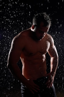 Stunning man with muscular body posing in rain, with naked torso, water drops on body