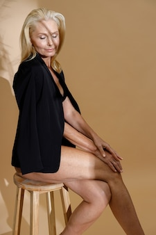 下着と目を閉じてポーズをとって上に古典的な黒のジャケットで見事な成熟したブロンドの女性
