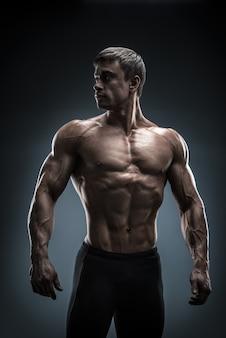 ポーズをとって後ろを振り返る見事な筋肉質の若い男性のボディービルダー。黒の背景で撮影したスタジオ。