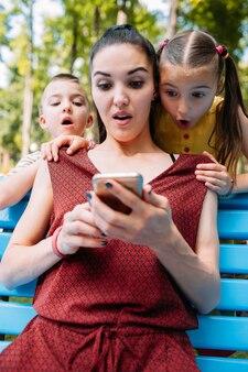 Потрясающие новости. семья удивлена чему-то, что они видят на экране телефона
