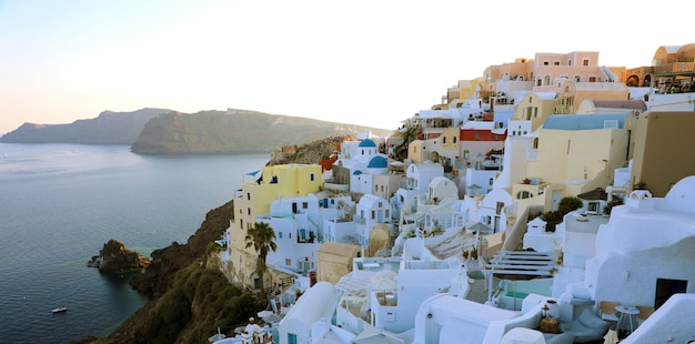 Stunning panoramic view of santorini island with white houses and blue domes on famous greek resort oia, greece, europe.