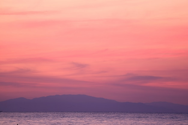 Stunning pastel pink and purple sunrise sky over the gulf of thailand with the mountain range in the backdrop