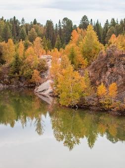 Потрясающее фото осенней листвы, отраженной на озере с зеркальной водной гладью.