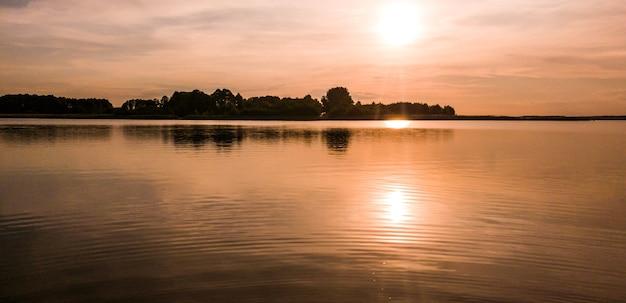 청동 저녁 석양에 잔잔한 수면과 갈대가있는 여름 호수의 멋진 그림 같은 풍경. 야생 동물의 아름다움 개념