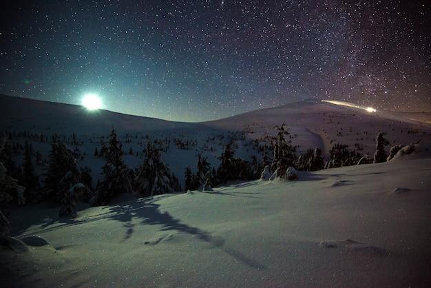 見事な絵のように美しい冬の風景、雪をかぶった丘や木々が星空に立ち向かい、太陽がのぞきます。冬の山々の日の出の概念