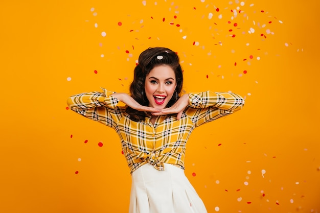 Stunning pinup girl expressing positive emotions. studio shot of lovely brunette woman in checkered shirt posing under confetti.