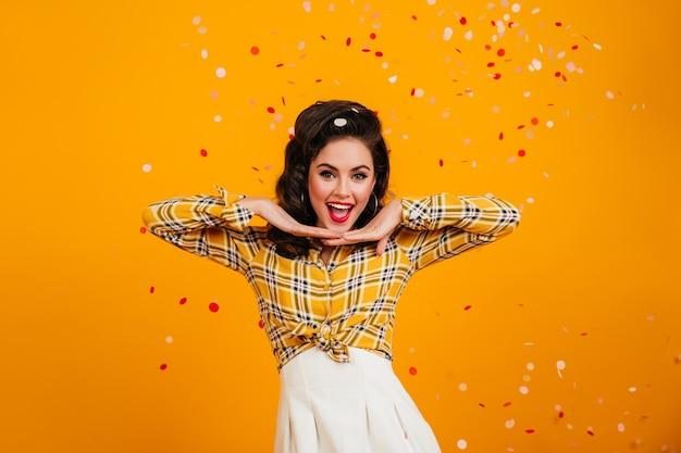 긍정적 인 감정을 표현하는 멋진 핀업 소녀. 색종이 아래 포즈 체크 무늬 셔츠에 사랑스러운 갈색 머리 여자의 스튜디오 샷.