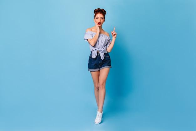 Сногсшибательная женщина кинозвезды указывая пальцем вверх. вид в полный рост удивленной рыжей дамы в джинсовых шортах.
