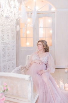 Stunning pregnant woman in pink dress rests on couch in a white room
