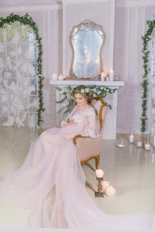 Stunning pregnant woman in pink dress rests on couch surrounded with shiny candles