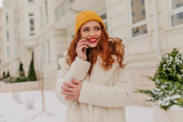 전화와 함께 포즈를 취하는 동안 웃 고 멋진 red-haired 아가씨. 겨울 아침에 거리에 서있는 매력적인 생강 여자의 야외 촬영.