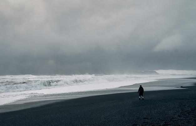 Потрясающие пейзажи, черный песчаный берег, сильные штормовые волны, пасмурное серое небо. мужчина на берегу смотрит на морской пейзаж. путешествия, отдых, туризм.