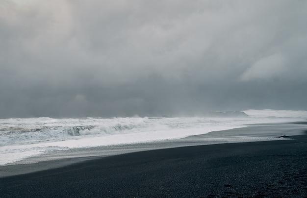 Потрясающие пейзажи, черный песчаный берег, сильные штормовые волны, пасмурное серое небо. морской пейзаж. путешествия, отдых, туризм.