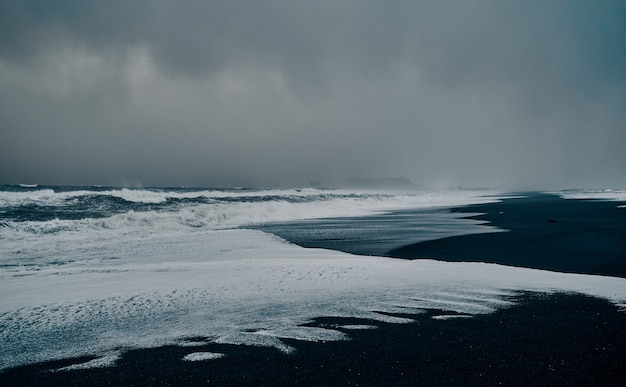 見事な景色、黒い砂浜、強い嵐の波、曇った灰色の空。海景。