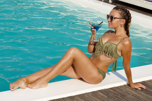 Stunning sexy young woman relaxing by the swimming pool with a drink.