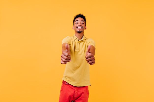 진지한 감정을 표현하는 멋진 단발 남자. 엄지 손가락을 보여주는 노란색 티셔츠에 영감을받은 남자.