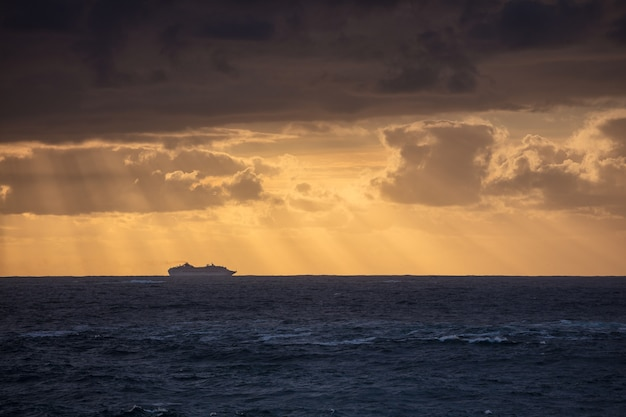 Stunning shot of the calm blue ocean and the silhouette of a ship under a cloudy sky during sunset