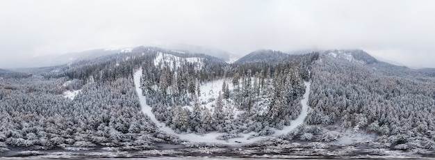 寒い冬の朝に濃い霧に覆われた木々と白い雪の崖の見事なスキーパノラマ