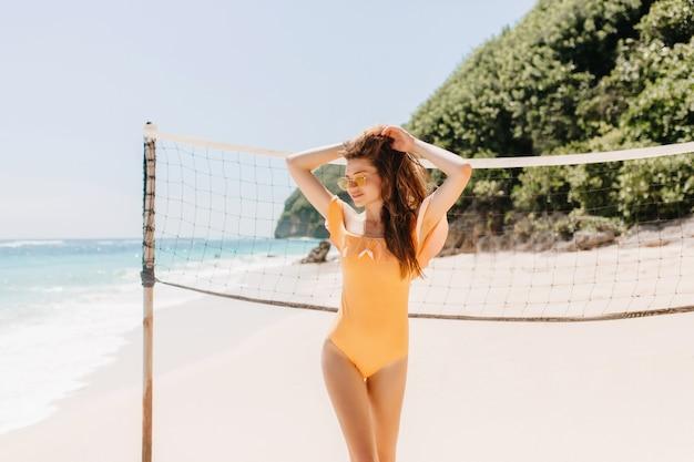 バレーボールセットの近くでふざけてポーズをとっている茶色の髪の見事なスリムな女の子。ビーチで踊る黄色い水着の愛らしい女性の屋外の肖像画