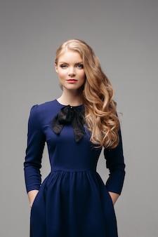 Stunning slim model in bright blue dress and black heels.