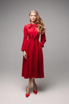 밝은 빨간 드레스와 검은 발 뒤꿈치에 멋진 슬림 모델.