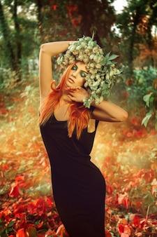 屋外の頭に赤毛とホップの花輪を持つ見事なスリムな若い大人の女性