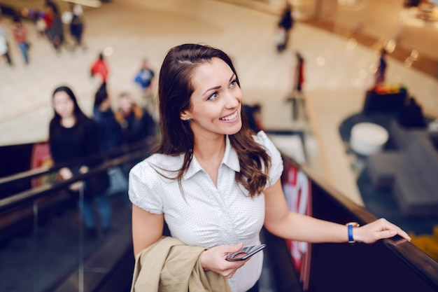 Stunning smiling brunette climbing the escalator, holding beige jacket and smart phone while looking away.