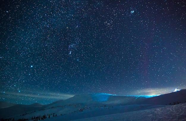 맑은 겨울 밤에 스키 리조트 위에 푸른 안개 속의 멋진 별이 빛나는 하늘이 있습니다.