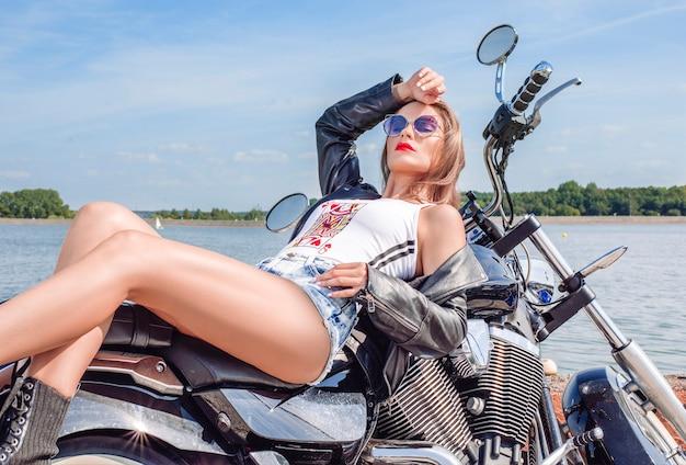 블랙 가죽 재킷과 데님 반바지를 입은 멋진 스타일의 금발이 거대한 오토바이 근처에서 포즈를 취하고 있습니다. 모터스포츠, 관광, 패션 스타일의 개념. 혼합 매체