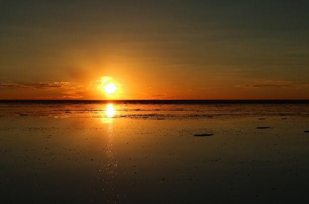 Stunning sunset reflection on the flooded uyuni salt flats of bolivia, south america