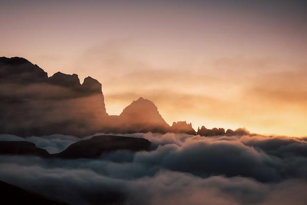 Потрясающий закат под скалами, наполненными плотным туманом.