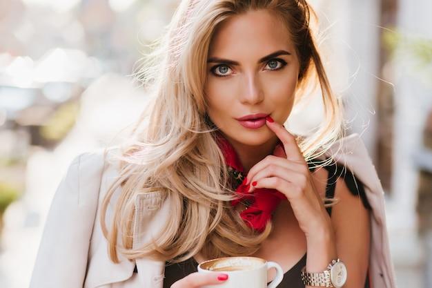 손가락으로 장난스럽게 입술을 만지고 포즈를 취하는 멋진 무두질 된 아가씨. 차 한잔 들고와 관심을 찾고 예쁜 금발 소녀