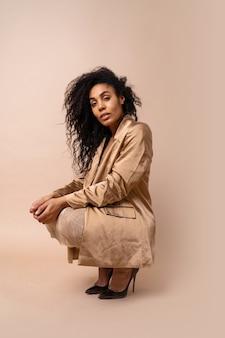 Splendida modella abbronzata con voluminosa acconciatura riccia in abito dorato lucido e giacca di raso in posa.