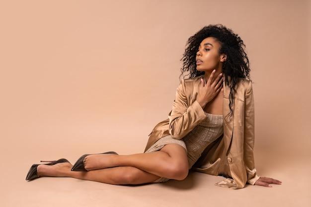 Splendida modella abbronzata con voluminosa acconciatura riccia in abito dorato lucido e blazer di raso seduto sul pavimento beige