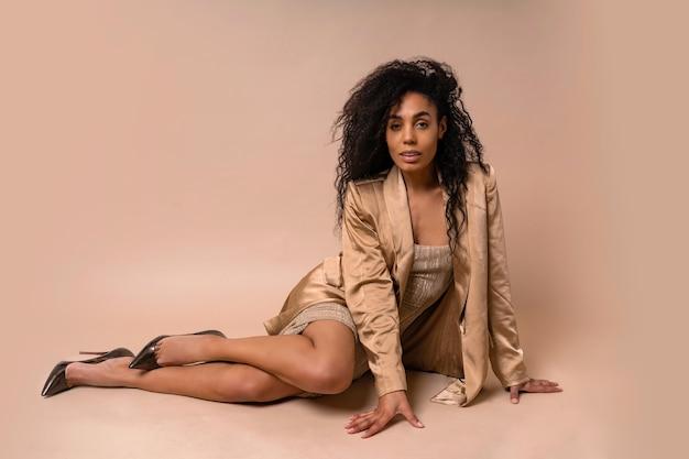 Splendida modella abbronzata con voluminosa acconciatura riccia in abito dorato lucido e giacca di raso seduta.
