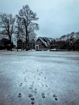 Stunning view of footprints in the snowy street heading to a big house with big windows and trees