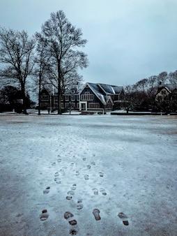 大きな窓と木がある大きな家に向かう、雪に覆われた通りの足跡の素晴らしい景色