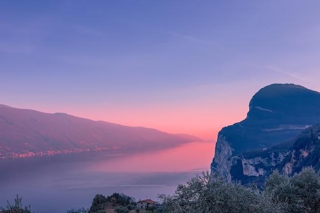 夕方の霧と夕日の光の中のガルダ湖の見事な景色。山間の町トレモージネからの眺め